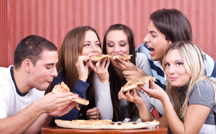 Pizza Near IUP – Five college students male and female smiling and eating pizza from a small round table