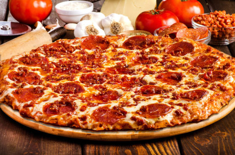 Gourmet Italian style pizza with pepperoni, bacon, lots of cheese on a wood pizza tray and fresh tomatoes garlic pepperoni and flour in the background