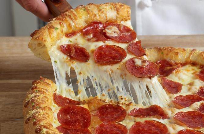 Another image of a beautiful pepperoni pizza, a close up shot the pepperoni is a delicious red and the cheese is white and yello and redish and lite brown. Yummy!
