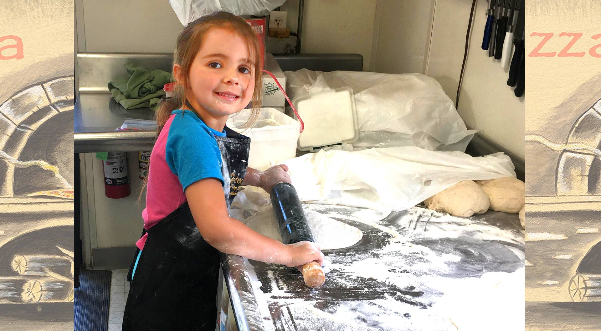a picture of the grand daughter of the owner Val, she is rolling out some pizza dough, standing ona stool, she looks to be about 5 years old, it's a very cute picture